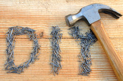 DIY (do it yourself) text from small nails and hammer. On wooden desk background Stock Image