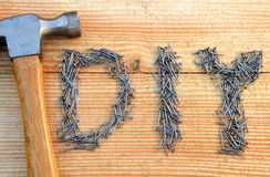 DIY (do it yourself) text from small nails and hammer. On wooden desk background Royalty Free Stock Image