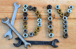 DIY (do it yourself) text from small nuts and spanners. On wooden desk background Stock Photo