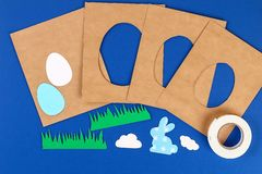 Diy Easter cards from paper. Volume greeting cards with a bunny, egg on blue background. 3d. Gift idea, decor Spring, Easter. Step by step. Top view. Process royalty free stock photo