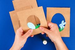 Diy Easter cards from paper. Volume greeting cards with a bunny, egg on blue background. 3d. Gift idea, decor Spring, Easter. Step by step. Top view. Process stock photo