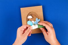 Diy Easter cards from paper. Volume greeting cards with a bunny, egg on blue background. 3d. Gift idea, decor Spring, Easter. Step by step. Top view. Process royalty free stock images