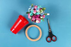 Diy Easter egg basket made of red plastic cup decorated with artificial flowers on blue background. Diy Easter egg basket made of red plastic cup decorated with royalty free stock images