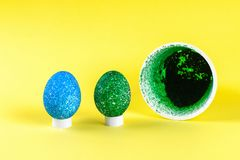 Diy Easter egg painted with colored rice on a yellow background. The decor of eggs for Easter stock photos