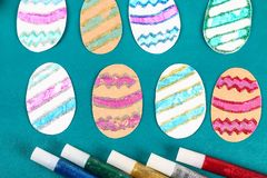 Diy Easter eggs made of cardboard and potato stamp, Easter greeting card on green background. Gift idea, decor Spring, Easter. Step by step. Top view. Process stock photo