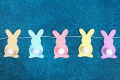 Diy Easter garland bunnies, flags EASTER made paper blue background. Gift idea, decor Spring, Easter. Diy Easter garland bunnies, flags with letters EASTER made stock images