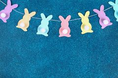 Diy Easter garland bunnies, flags EASTER made paper blue background. Gift idea, decor Spring, Easter. Diy Easter garland bunnies, flags with letters EASTER made royalty free stock photo