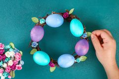 Diy Easter wreath of twigs, painted eggs and artificial flowers on a green background. Gift idea, decor Spring, Easter. Step by step. Top view. Process kid stock photography