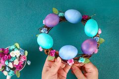Diy Easter wreath of twigs, painted eggs and artificial flowers on a green background. Gift idea, decor Spring, Easter. Step by step. Top view. Process kid stock images