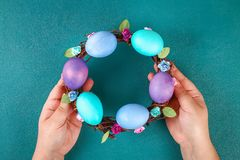 Diy Easter wreath of twigs, painted eggs and artificial flowers on a green background. Gift idea, decor Spring, Easter. Step by step. Top view. Process kid royalty free stock images