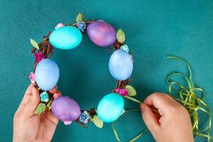 Diy Easter wreath of twigs, painted eggs and artificial flowers on a green background. Gift idea, decor Spring, Easter. Step by step. Top view. Process kid stock photo