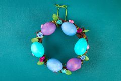 Diy Easter wreath of twigs, painted eggs and artificial flowers on a green background stock photos
