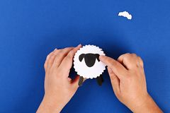 Diy Eid al adha lamb sheep sweet candy paper, wooden sticks for ice cream on blue background stock photography