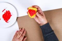 DIY Gåvainpackning för valentin dag Gåva för Kraft papper och potatisstämpel i formen av en hjärta och en röd målarfärg att göra  royaltyfri foto