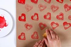 DIY Gåvainpackning för valentin dag Gåva för Kraft papper och potatisstämpel i formen av en hjärta och en röd målarfärg att göra  royaltyfria bilder