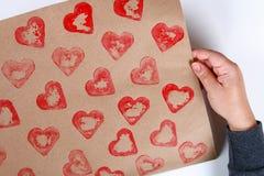 DIY Gåvainpackning för valentin dag Gåva för Kraft papper och potatisstämpel i formen av en hjärta och en röd målarfärg att göra  royaltyfri bild