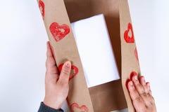 DIY Gåvainpackning för valentin dag Gåva för Kraft papper och potatisstämpel i formen av en hjärta och en röd målarfärg att göra  fotografering för bildbyråer