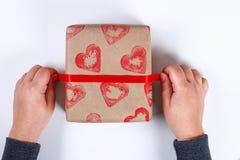 DIY Gåvainpackning för valentin dag Gåva för Kraft papper och potatisstämpel i formen av en hjärta och en röd målarfärg att göra  arkivbild