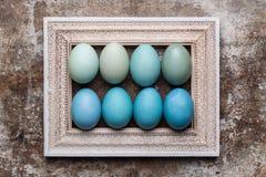 DIY gefärbte verschiedene Schatten des blauen hölzernen Spotts Ostereier und des Bilderrahmens der Weinlese oben Lizenzfreies Stockbild