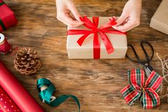 DIY Gift Wrapping. Woman wrapping beautiful christmas gifts on rustic wooden table. Overhead view of christmas wrapping station royalty free stock photos