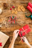 DIY Gift Wrapping. Woman wrapping beautiful red christmas gifts on rustic wooden table. Overhead point of view of christmas stock image