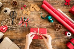 DIY Gift Wrapping. Woman wrapping beautiful red christmas gifts on rustic wooden table. Overhead point of view. royalty free stock photo