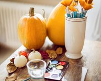 DIY Halloween concept. Art and craft, decorating Halloween pumpkins. Color pallete, paintbrush and pumpkins on a table. DIY Halloween concept. Art and craft stock photography