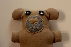 A DIY Hand-stitched Brown Teddy bear with Blanket Stitching and Black Button Eyes. Top part of a DIY Hand-stitched Brown Teddy bear with Blanket Stitching and Stock Photo