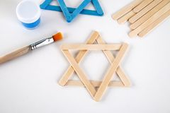 DIY. Hanukkah decor. Star of David from ice cream sticks on a white wooden table. Guide, step by step on the photo. Diy on. Hanukkah royalty free stock images