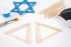 DIY. Hanukkah decor. Star of David from ice cream sticks on a white wooden table. Guide, step by step on the photo. Diy on. Hanukkah stock image