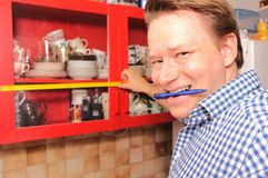 DIY. Happy man planning some home improvement in his kitchen Royalty Free Stock Photography