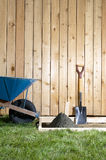 DIY, home concreting project with cement tools. A backyard, DIY, home garden concreting project with wheelbarrow, shovel, wooden fence, wet cement and form work Royalty Free Stock Image