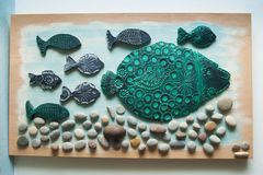 Diy home decoration hobby idea on wooden board from ceramics and. Little stones painted and decorated stock photography