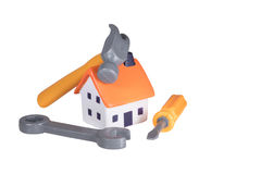 DIY and home improvements concept. With a hammer, spanner and screwdriver arranged around a small model house isolated on white stock photo