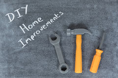 DIY and Home Improvements concept. With handwritten text on slate or a chalkboard with a hammer, spanner and screwdriver viewed from above royalty free stock image