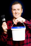 DIY home owner holding up paint and a paintbrush Royalty Free Stock Image