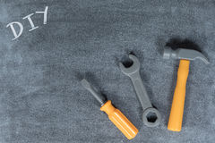DIY home renovations and maintenance concept. With handwritten tex in the corner of a chalkboard opposite a screwdriver, hammer and spanner with copy space Royalty Free Stock Photos