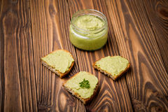 Diy homemade avocado chilli paste. Natural homemade DIY vegan very healthy green paste made of avocado, millet gruel, chilli, garlic and parsley on bread and Stock Images
