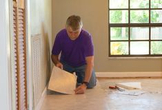 DIY homeowner man or professional installing vinyl tile flooring. DIY homeowner man or professional maintenance and installer installing new tan vinyl tile stock image
