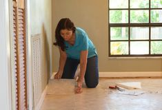 DIY homeowner woman or professional installing vinyl tile flooring. DIY homeowner woman or professional maintenance and installer installing new tan vinyl tile royalty free stock photography