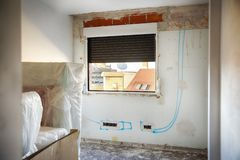 DIY, house indoor improvements in a messy room construction. Renovated windows, blue lines to electrical installation and wall. Chasing reform renovation repair royalty free stock photo
