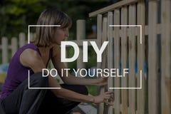DIY-Konzept mit einer Frau, die einen Gartenzaun errichtet Stockfotografie