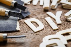 DIY Letters Woodwork. DIY Do It Yourself letters woodwork with graver and sandpaper on the table stock photos