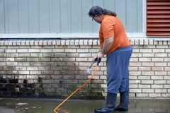 Man powerwashing mold of wall - DIY royalty free stock images