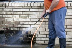 Man powerwashing mold of wall - DIY stock images