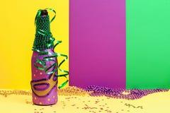 Diy Mardi Gras bottle purple adhesive paper, green bead, carnival mask, sequins yellow background. Diy Mardi Gras bottle purple self adhesive paper, green bead stock photos