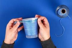 Diy pencil holder plastic glass sour cream, yogurt wrapped thread blue background royalty free stock photo