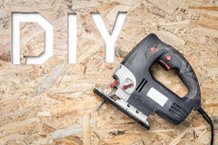 DIY project. DIY acronym cut out in OSB panel with electric jigsaw royalty free stock photo
