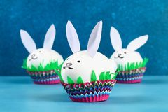 Diy rabbit from easter eggs on blue background. Gift ideas, decor Easter, spring. Handmade. White easter egg bunny, grass crepe paper, cup muffin cupcake. Step royalty free stock photo