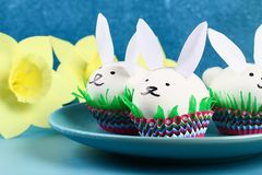 Diy rabbit from easter eggs on blue background. Gift ideas, decor Easter, spring. Handmade. White easter egg bunny, grass crepe paper, cup muffin cupcake. Step stock photography